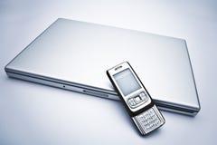 Ordenador portátil con el teléfono celular Imagenes de archivo