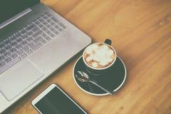 Ordenador portátil con el teléfono del smarth en el escritorio de madera en roo del negocio fotos de archivo libres de regalías