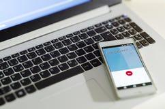 Ordenador portátil con el teléfono móvil y la llamada del encargado de los personales para simbolizar una advertencia o una termi Foto de archivo libre de regalías