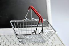 Ordenador portátil con la cesta de compras Fotografía de archivo