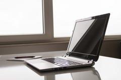 Ordenador portátil con la mofa blanca de la pantalla encima de la plantilla Escritorio de oficina con el ordenador; taza y pluma  foto de archivo