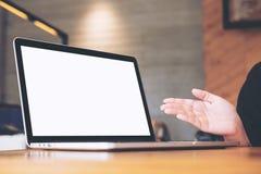 Ordenador portátil con la pantalla blanca en blanco en la tabla de madera con la mano abierta del ` s de la mujer para la present Fotos de archivo