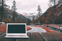 Ordenador portátil con la pantalla en blanco en la tabla de madera con el bosque en montaña Foto de archivo