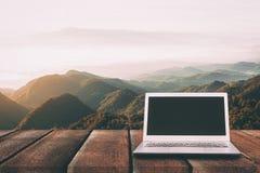 Ordenador portátil con la pantalla en blanco en la tabla de madera con el bosque en montaña Foto de archivo libre de regalías