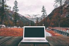 Ordenador portátil con la pantalla en blanco en la tabla de madera con el bosque en montaña Fotografía de archivo libre de regalías