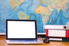 Ordenador portátil con la pantalla vacía en blanco en fondo del mapa del mundo fotografía de archivo
