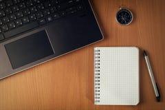 Ordenador portátil con la pila de carpetas en la tabla en el fondo de madera imagen de archivo