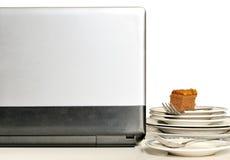 Ordenador portátil con la pila de placas sucias en el escritorio de trabajo Imagen de archivo