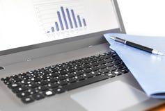 Ordenador portátil con la pluma y la libreta Imagen de archivo