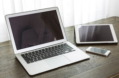 Ordenador portátil con la tableta y el teléfono elegante en la tabla Fotografía de archivo libre de regalías