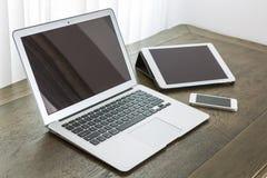 Ordenador portátil con la tableta y el teléfono elegante en la tabla Foto de archivo