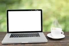 Ordenador portátil con la taza de café en de madera con el defocus de Garde fotografía de archivo libre de regalías