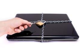 Ordenador portátil con las cadenas y el candado. Foto de archivo