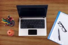 Ordenador portátil con las fuentes de escuela Foto de archivo libre de regalías