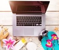 Ordenador portátil con los accesorios de la playa en la cubierta de madera Fotos de archivo libres de regalías