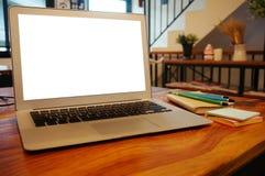 Ordenador portátil con mofa encima de la pantalla en blanco en la tabla de madera delante del cof imagen de archivo libre de regalías