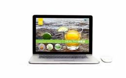 Ordenador portátil con sitio web sano en la pantalla en fondo, dieta de la infusión y detox blancos aislados imagen de archivo libre de regalías
