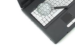 Ordenador portátil con un vidrio del magnificar imagen de archivo libre de regalías