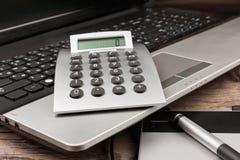 Ordenador portátil con una calculadora y una tableta gráfica en una tabla de madera Imagen de archivo libre de regalías