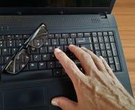 Ordenador portátil con vidrios y un fondo de madera foto de archivo libre de regalías