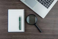 Ordenador portátil, cuaderno y el magnificar y pluma en el escritorio del trabajo Fotos de archivo