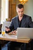 Ordenador portátil de With Cellphone And del hombre de negocios adentro fotografía de archivo libre de regalías
