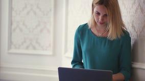 Ordenador portátil de la abertura de la mujer joven para Internet de la ojeada en interior del sitio almacen de metraje de vídeo