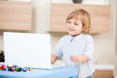 Ordenador portátil de la mirada del niño Foto de archivo libre de regalías