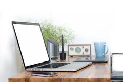 Ordenador portátil de la pantalla en blanco en el escritorio de madera Foto de archivo libre de regalías