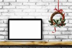 Ordenador portátil de la pantalla en blanco en la pared de ladrillo blanca con la guirnalda de la Navidad foto de archivo