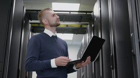 Ordenador portátil de la tenencia del hombre y hacer el diagnóstico del datacenter en sitio del servidor almacen de metraje de vídeo
