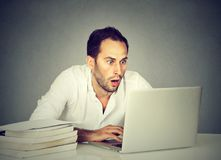 Ordenador portátil de observación chocado del hombre mientras que estudia fotos de archivo