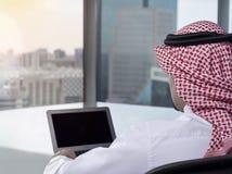 Ordenador portátil de observación del hombre de Arabia Saudita en la comtemplación del trabajo foto de archivo