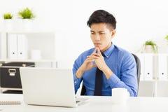 Ordenador portátil de observación y pensamiento del hombre de negocios asiático Imágenes de archivo libres de regalías
