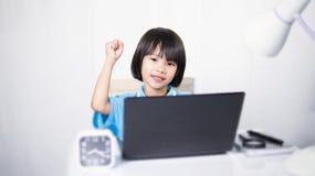 Ordenador portátil de pensamiento y que mecanografía del niño lindo imagenes de archivo
