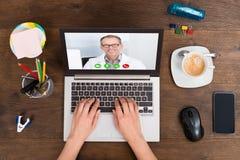 Ordenador portátil de Person Videochatting With Doctor On Foto de archivo libre de regalías