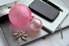 Ordenador portátil de plata con las bolas rosadas de la Navidad, las decoraciones, el espacio androide del teléfono celular, del  Fotografía de archivo