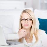 Ordenador portátil de Sit On The Sofa With de la mujer joven Imagen de archivo libre de regalías