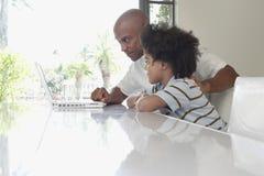 Ordenador portátil de And Son Using del padre en la mesa de comedor Imagen de archivo
