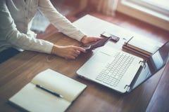 Ordenador portátil de trabajo de la mano de la mujer de negocios en el escritorio de madera fotos de archivo libres de regalías