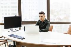 Ordenador portátil de trabajo del al del hombre de negocios en sitio moderno de la oficina Imagenes de archivo