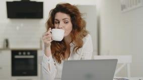 Ordenador portátil de trabajo de la mujer feliz en el lugar de trabajo remoto Té de consumición de la señora joven en casa almacen de video