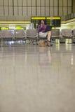 Ordenador portátil de Using Cellphone And de la empresaria en pasillo del aeropuerto imágenes de archivo libres de regalías