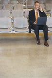 Ordenador portátil de Using Cellphone And del hombre de negocios en pasillo foto de archivo