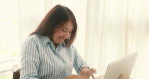 Ordenador portátil del éxito de la mujer que anima mayor almacen de metraje de vídeo