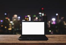 Ordenador portátil del ordenador en el escritorio de madera con las luces de Bokeh de la ciudad en el fondo de la noche Pantalla  Imágenes de archivo libres de regalías