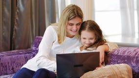 Ordenador portátil del reloj de la hija de la mamá del ocio de la familia junto almacen de video