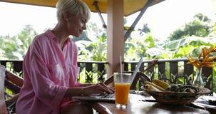 Ordenador portátil del uso de la chica joven que se sienta en la tabla en la terraza del verano, charla hermosa de la mujer en lí almacen de metraje de vídeo