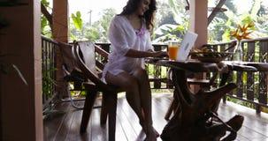 Ordenador portátil del uso de la chica joven que se sienta en la tabla en la terraza del verano, charla hermosa de la mujer en lí metrajes