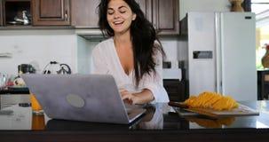 Ordenador portátil del uso de la muchacha en la cocina que charla el interior moderno de la casa del estudio en línea de la mujer almacen de metraje de vídeo